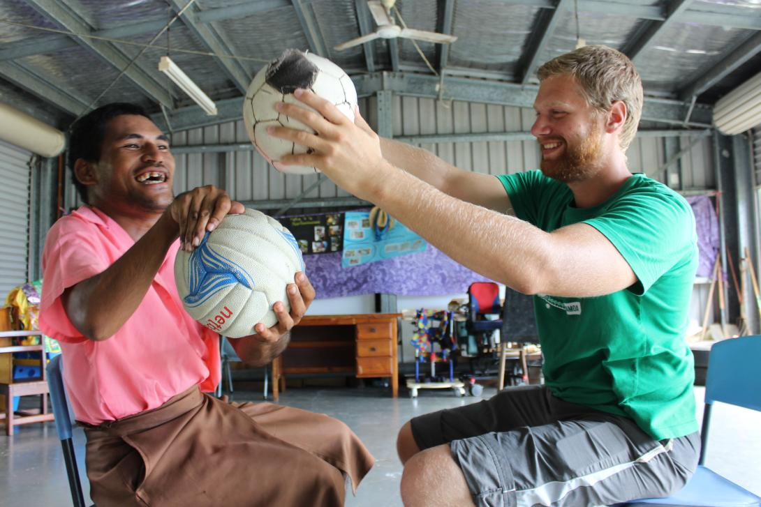 A physiotherapy volunteer uses a soccer ball as part of a therapy session on an ethical volunteering opportunity abroad.